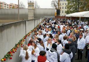 ベルリンの壁崩壊から30年を迎え、保存されている壁にバラの花を手向ける人たち=9日、ドイツ・ベルリン(ロイター=共同)
