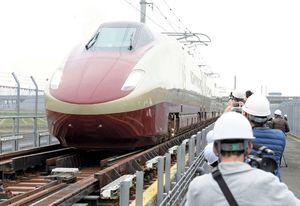 試験走行でJR新八代駅を過ぎ、軌間変換装置の上を通過し在来線のレール幅に切り替えるフリーゲージトレイン=2017年3月、熊本県八代市