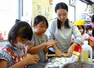 子どもたちに本格ギョーザ作りを指導したジア・ワンルさん(右)=佐賀市の循誘公民館
