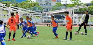 学年ごとに分かれたミニゲームで懸命にボールを追う韓国と佐賀の子どもたち=佐賀市の県総合運動場陸上競技場
