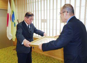 紺綬褒章の章記(賞状)を秀島敏行市長から受け取る古賀常次郎さん(左)=佐賀市役所