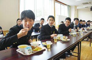 佐賀牛のハンバーグをおいしそうに頰張る男子生徒=大町町の大町ひじり学園