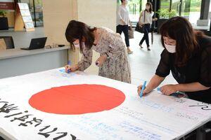林大地選手への応援メッセージを書き込む人たち=佐賀市の佐賀県庁
