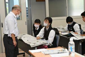 多久島文樹・NIE推進担当デスク(左)と紙面から気になるニュースを探す佐賀商高の生徒たち=佐賀市の同校
