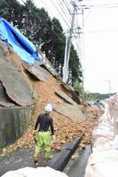 大雨の影響で幅20㍍、高さ12㍍にわたって斜面が崩落した現場。被害の拡大を防ぐ応急処置が進められた=伊万里市黒川町の国道204号