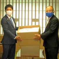 秀島敏行市長にマスクを手渡す佐賀青年会議所の西村祐二郎理事長(左)=佐賀市役所