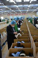 冷凍網ノリの品質をチェックする業者=佐賀市の佐賀海苔共販センター
