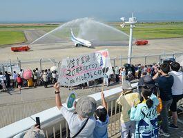 開港20周年を記念した放水アーチで迎えられる羽田-佐賀便。大勢の人が展望デッキで見守った=28日午前9時10分ごろ、佐賀市川副町の佐賀空港