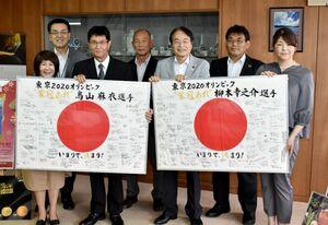 市民からの寄せ書きを受け取った鳥山麻衣選手の両親(前列左側)と柳本幸之介選手の母親(前列右端)=伊万里市役所