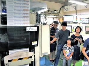 新聞の刷り上がる様子に見入る子ども記者たち=佐賀市天神の佐賀新聞社