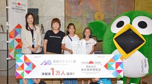 来館者1万人目となった野下智子さん(左から2人目)ら3人=鳥栖市神辺町の鳥栖サテライト館