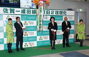 記念セレモニーで、くす玉を割って成田線の増便を祝う関係者=佐賀市川副町の佐賀空港