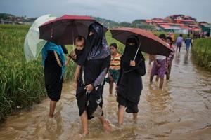 バングラデシュで、難民キャンプ近くの水浸しの道を歩くロヒンギャの女性たち=17日(AP=共同)