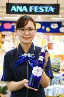 記念ボトルを手にするANA FESTAスタッフ=佐賀市の佐賀空港