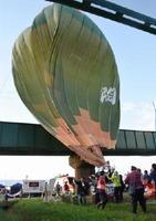 地上からロープで引っ張られる気球=いずれも佐賀市の嘉瀬川河川敷