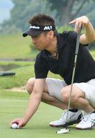 真剣なまなざしで芝目を読む選手=多久市の佐賀クラシックゴルフ倶楽部