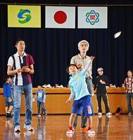 自作の紙飛行機を力強く飛ばす子どもたち=佐賀市の開成小体育館