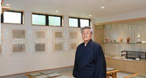 国重要文化財のレプリカが並ぶ資料展示室と武雄哲司宮司=武雄市の武雄神社