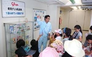 プリンや乳飲料ができる過程を熱心に聞く参加者ら=佐賀市大和町の佐賀グリコ乳業工場