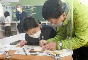 肥前吉田焼窯元協同組合の副島孝信さん(右)に教わりながら、磁器質タイルの製作をする生徒=嬉野市の大野原中学校