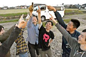 パシフィックカップと日本選手権の2冠達成を、チームのクルーと喜ぶ上田諭選手(右から3人目)=佐賀市の嘉瀬川河川敷付近