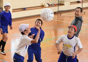 笑顔でバレーボールを楽しむ児童と教諭=神埼市神埼町の西郷小