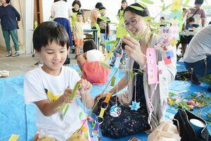 たなばたまつりでカラフルな飾りをササ竹に取り付ける親子=有田町役場