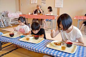 4カ月ぶりに再開した「佐志食堂」でカツカレーを味わう親子連れ=唐津市の佐志公民館