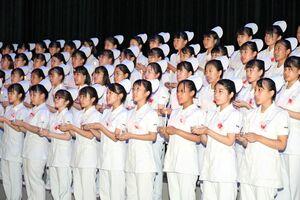 キャンドルを持ち、ナイチンゲール誓詞を唱和する生徒たち=佐賀市文化会館