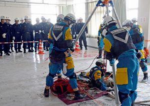 床に脱出口を開けて救出する訓練=鹿島市の鹿島市民会館
