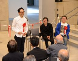 開会式であいさつする(左から)池田学さん、葉山有樹さん、八谷和彦さん=佐賀市の県立美術館