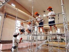 家を建てる際の足場を組み立てる多久高の女子生徒たち=多久市の県立産業技術学院