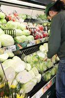 野菜を売り場に並べる店員。長雨の影響で葉物を中心に例年の2~3倍の価格になっている=佐賀市のアルタ開成店