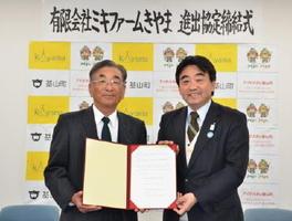 進出協定を結んだミキファームきやまの三木信雄社長(左)と松田一也町長=基山町役場