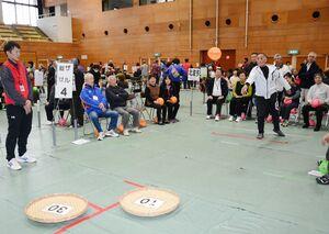 ザルめがけてガンバルーンボールを投げる参加者=唐津市の市文化体育館