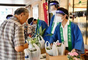 おそろいの法被を着て観葉植物などを販売する高志館高の生徒ら(右)=佐賀市の佐賀玉屋南館前
