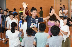 兵庫小の児童からハイタッチで見送られる高橋秀人選手=佐賀市の同校