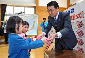 子どもたちにリンゴを手渡す雪田徹JA青森組合長=佐賀市中央児童センター