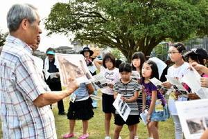 分教場の写真を見せながら説明をする平川さん(左)と話を聞く児童=佐賀市の大中島児童公園