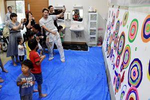 完成前の絵を見るミヤザキさんと子どもたち=嬉野市のデイサービス宅老所「芽吹き」