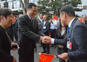 市役所職員の歓迎を受けながら、峰市長と握手する呉副秘書長(左)=唐津市役所