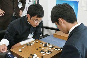 碁盤を見つめて集中する男子の決勝戦=佐賀市の日本棋院佐賀中央支部