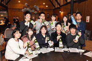 完成した「悠々知酔」の新酒を手にする学生ら=基山町の基山商店