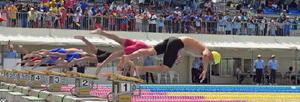 水泳男子200㍍リレー決勝で、合図とともに一斉に飛び込む選手たち=佐賀市の県水泳場(撮影・鶴澤弘樹)