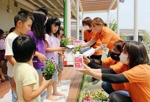 花の苗や消毒液などを園児たちに渡す小城市商工会女性部の役員たち=小城市芦刈町のあしかりこども園