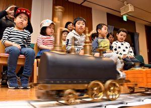 蒸気車ひな型のレプリカが走る様子を見つめる子どもたち=佐賀市川副町の佐野常民記念館
