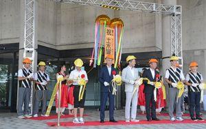 土木にちなんで、テープカットは軍手とヘルメットを着けて行われた=佐賀県立博物館