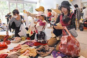 好みのデザインやサイズに合った子ども服を探す来場者(昨年の様子)