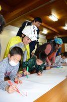 警察官らと一緒に垂れ幕を作る呼子小児童=唐津市呼子町の呼子公民館