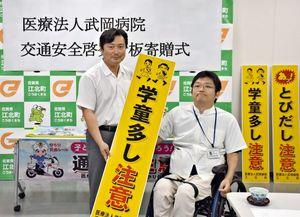 交通安全を啓発する看板を寄贈した武岡院長(右)と山田町長=江北町役場